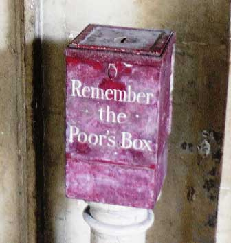 A red box that has the words Remember the Poors Box painted on it in white letters.