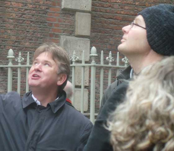 Richard Jones guiding a group of tour participants in the City of London. He is getting them to look up at a church tower.